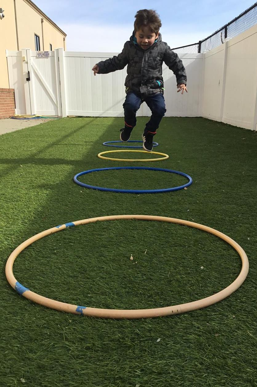 Happy Happens Here while hopping hula hoops